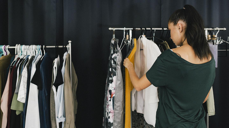 kvinna som tittar på kläder som hänger på ett ställ. foto: Adobestock